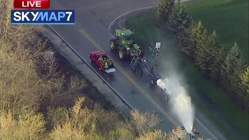 In this still image from video provided by ABC7 Chicago, a fire engine sprays water on a container o