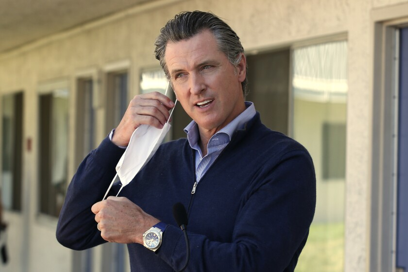 """Gov. Gavin Newsom removes his face mask before giving an update on the state's initiative to provide housing for homeless Californians to help stem the coronavirus, during a visit to a Motel 6 participating in the program in Pittsburg, Calif., Tuesday, June 30, 2020. Newsom announced that more than 15,000 rooms have been acquired and more than 14,000 people have been given places to stay statewide under the Project Room key program started in April. The governor also said he plans to announce on Wednesday plans to """"toggle back"""" the states stay-at-home order. (AP Photo/Rich Pedroncelli, Pool)"""