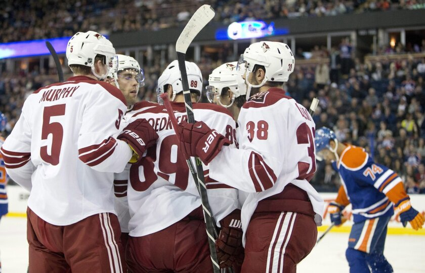 Arizona Coyotes' Connor Murphy (5), Mikkel Boedker (89), Lucas Lessio (38) and teammates celebrate a goal against the Edmonton Oilers during the first period of an NHL hockey preseason game, Wednesday, Oct. 1, 2014, in Edmonton, Alberta. (AP Photo/The Canadian Press, Jason Franson)