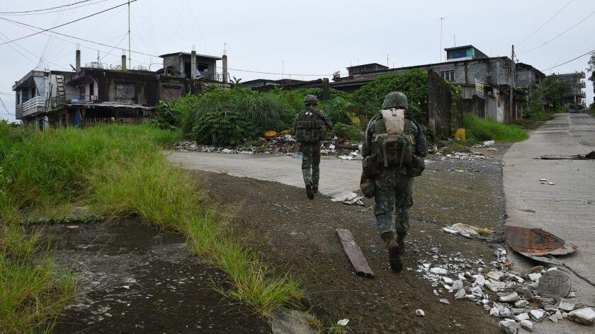 Philippine troops patrol a deserted neighborhood in Marawi on July 27, 2017.