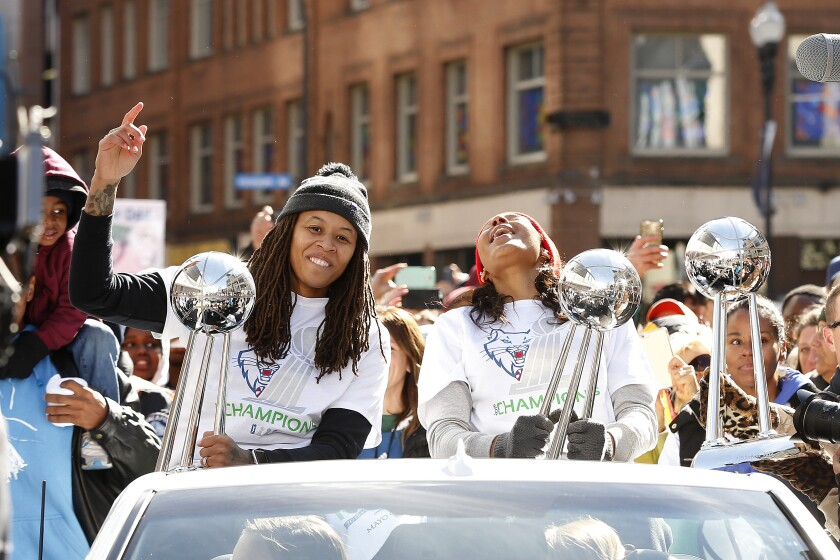 Minnesota Lynx basketball players Seimone Augustus and Maya Moore react to fan cheers during a parade.