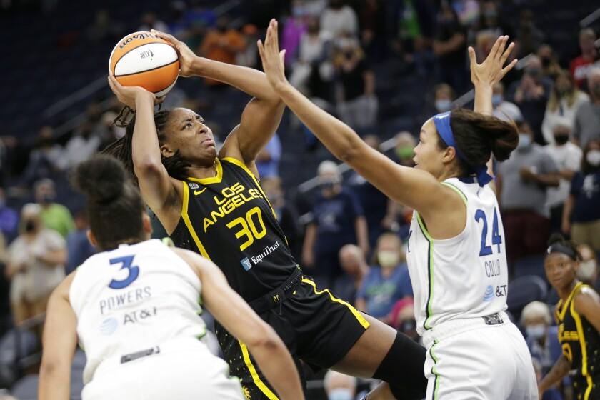 Sparks forward Nneka Ogwumike shoots over Minnesota Lynx forward Napheesa Collier and forward/guard Aerial Powers.