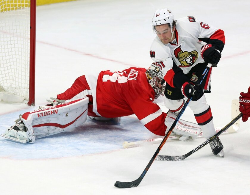Ottawa Senators' Mark Stone (16), right, attempts to get the puck around Detroit Red Wings' goaltender Petr Mrazek (34) during third period NHL hockey action, in Ottawa, on Saturday, Oct. 31, 2015. (Fred Chartrand/The Canadian Press via AP)