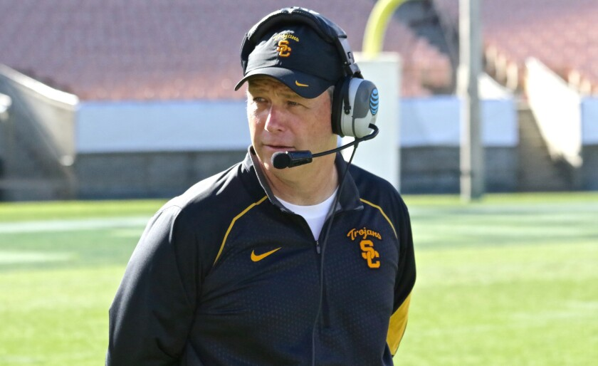 USC defensive coordinator Clancy Pendergast talks over the headset during a scrimmage period at the Coliseum on Aug. 15.