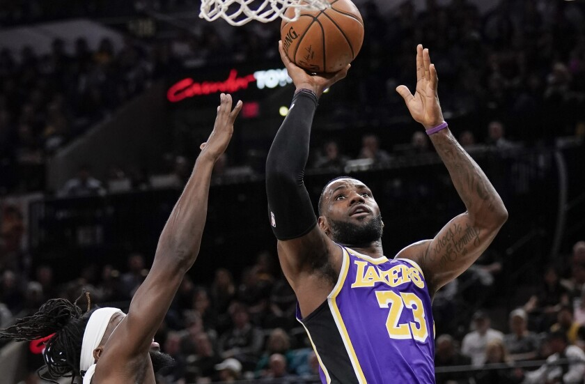 Lakers star LeBron James shoots over Spurs forward DeMarre Carroll.