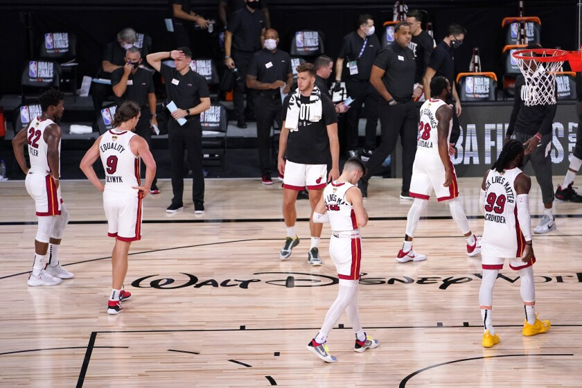 The Miami Heat's Jimmy Butler (22), Kelly Olynyk (9), Meyers Leonard, center rear, Tyler Herro, center front, Andre Iguodala (28) and Jae Crowder (99) walk off the court after their 124-114 loss to the Miami Heat in Game 2 of basketball's NBA Finals, Friday, Oct. 2, 2020, in Lake Buena Vista, Fla. (AP Photo/Mark J. Terrill)
