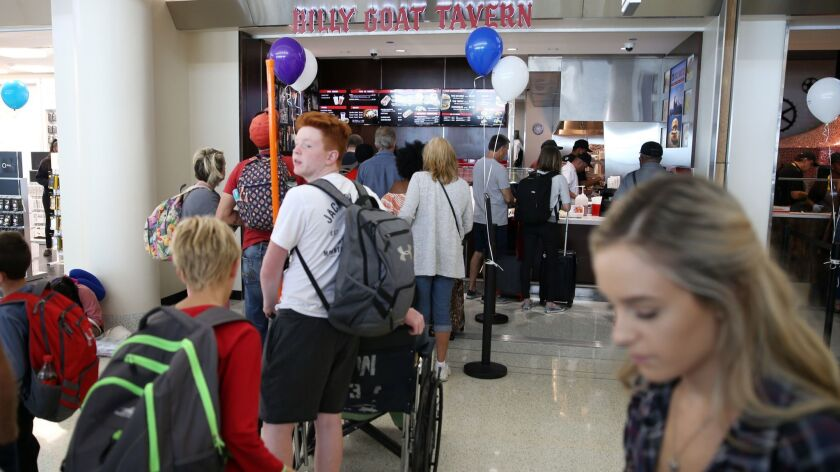 People line up to dine at the Billy Goat Tavern in a new food court at Midway Airport in Chicago on July 30, 2018.