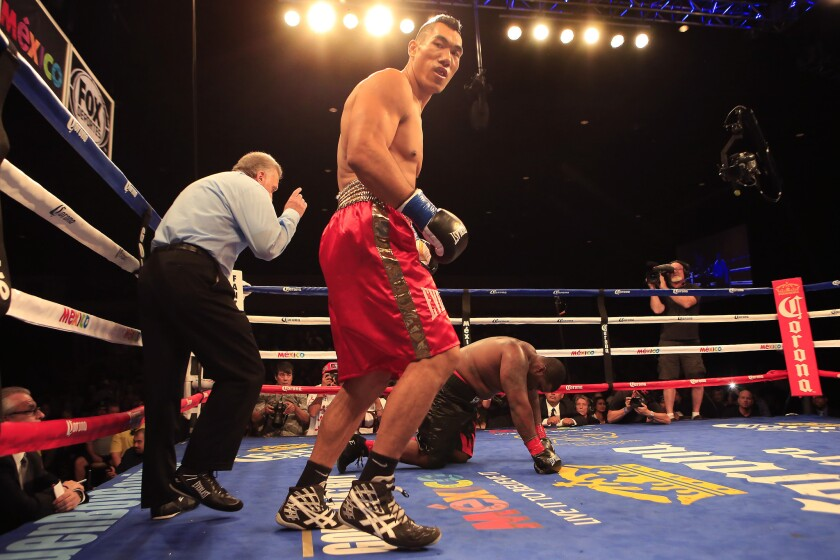 Taishan Dong moves away from opponent Tommy Washington as referee Jack Reiss delivers a ten-count in a heavyweight bout at Fantasy Springs Resort in Indio.