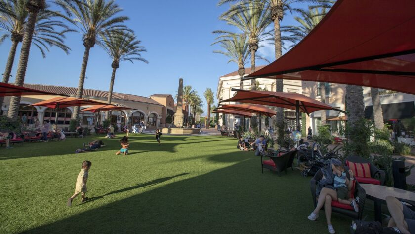 Shoppers take advantage of the redesigned Irvine Spectrum Center, where 30 new merchants have replaced the old Macy's anchor store. The Irvine Spectrum Center is spending heavily to keep people coming.