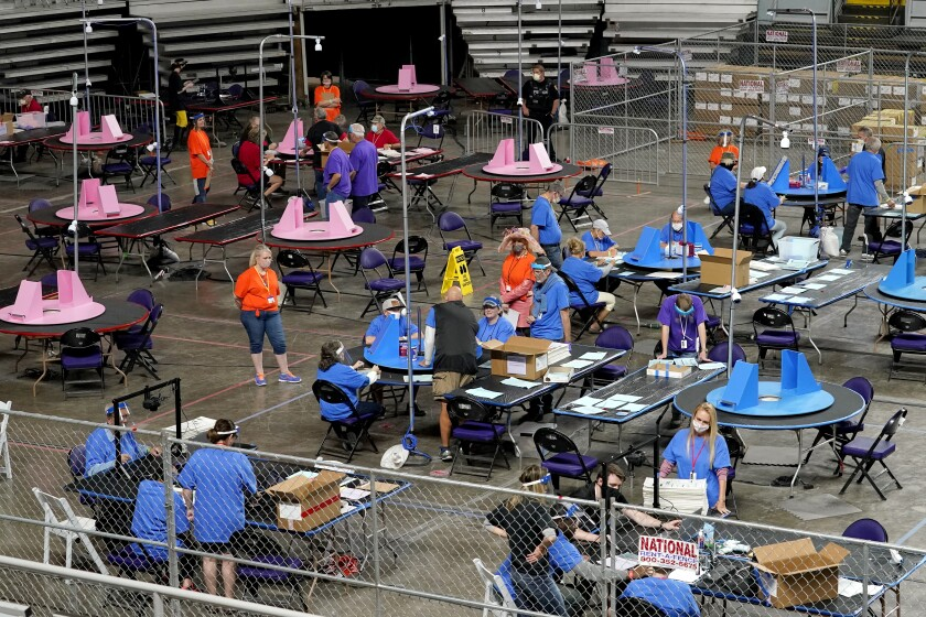 Ballots are examined and recounted by people at tablesin a fenced off area in a building.