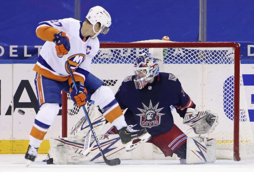 Anders Lee, left, of the New York Islanders attempts to deflect a shot but he is stopped by Igor Shesterkin, right, of the New York Rangers during the second period of an NHL hockey game Monday, Feb. 8, 2021, in New York. (Bruce Bennett/Pool Photo via AP)