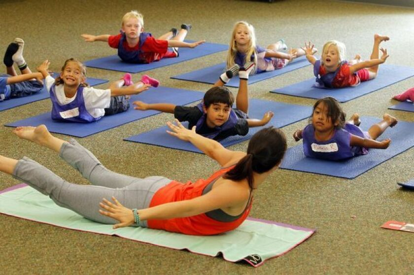 Yoga instructor Jackie Bergenon leads students at Paul Ecke Central Elementary School in Encinitas in a yoga exercise.