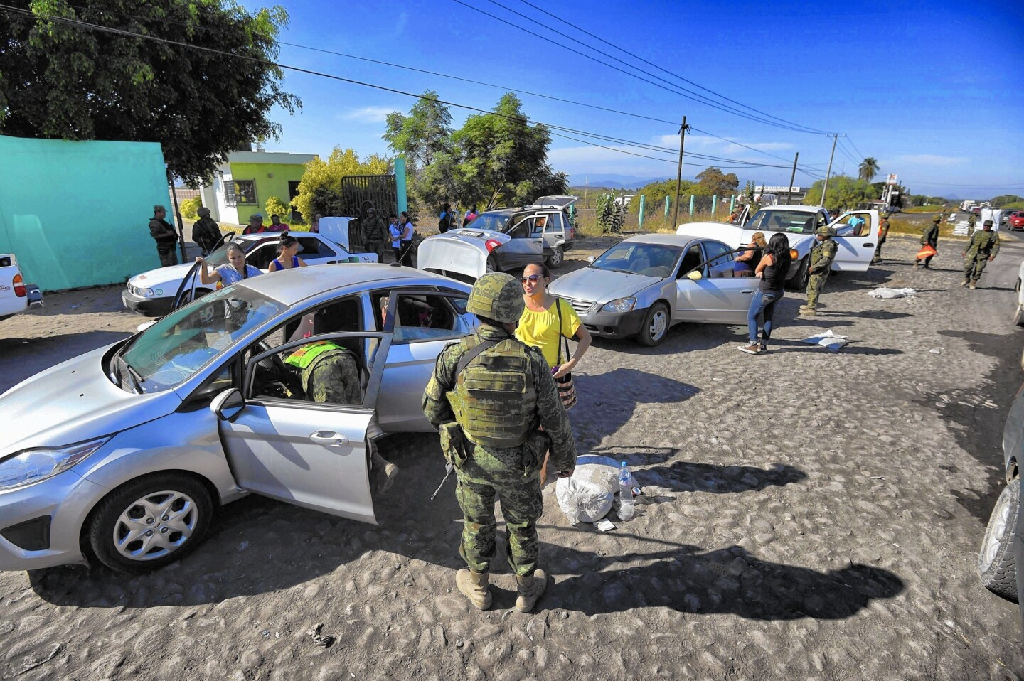 Soldiers inspect vehicles at a checkpoint at the entrance of Apatzingan in Mexico's violence-racked Michoacan state.