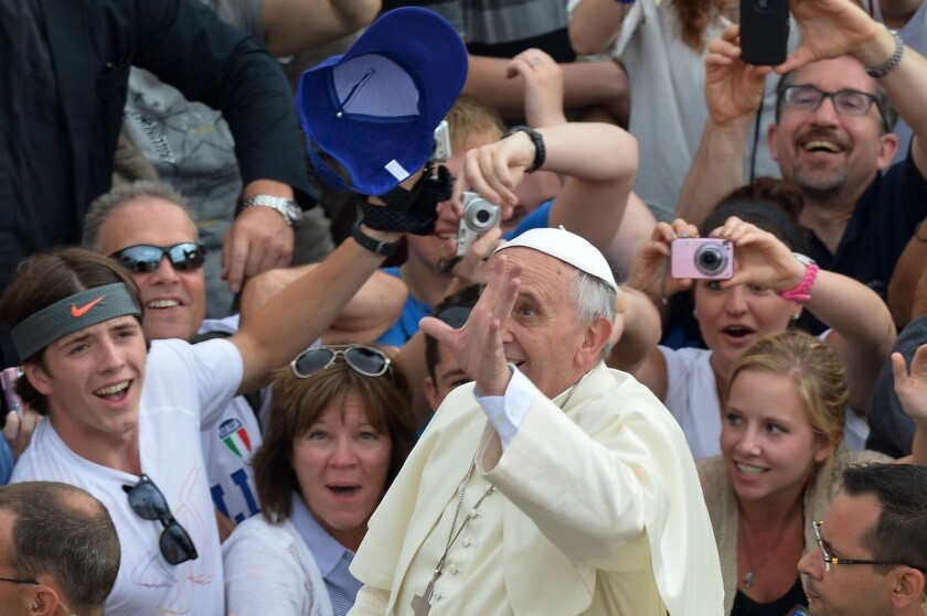 Pope Francis catches a cap thrown by a pilgrim during his general audience at St. Peter's Square on Wednesday.