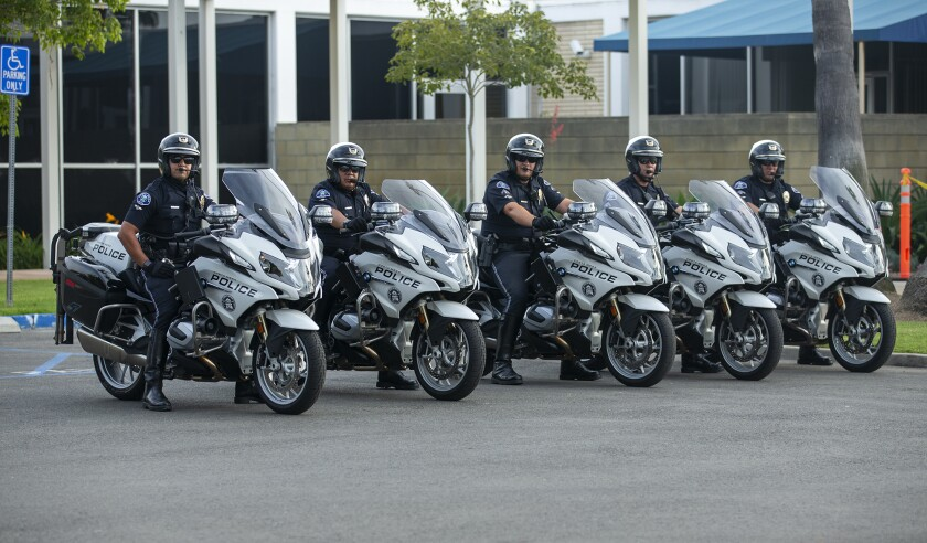 Costa Mesa Police Department motor officers line up across the street from protesters on Tuesday.