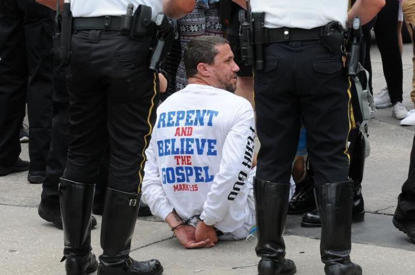 Agentes de la Policía mantienen esposado a un protestante religioso durante el acto conmemorativo a las 49 personas que perdieron la vida en la matanza perpetrada en 2016 en la discoteca gay Pulse, el lunes 12 de junio 2017, en Orlando, Florida (Estados Unidos). EFE/Gerardo Mora/Archivo