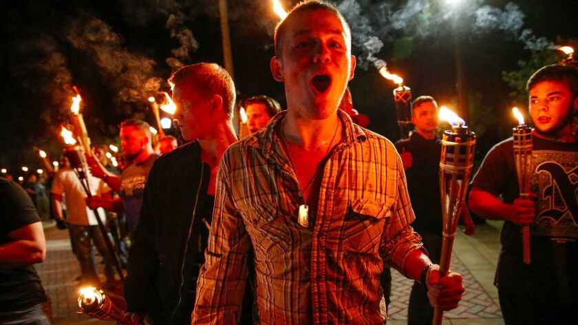 In this photo taken Friday, Aug. 11, 2017, multiple white nationalist groups march with torches thro