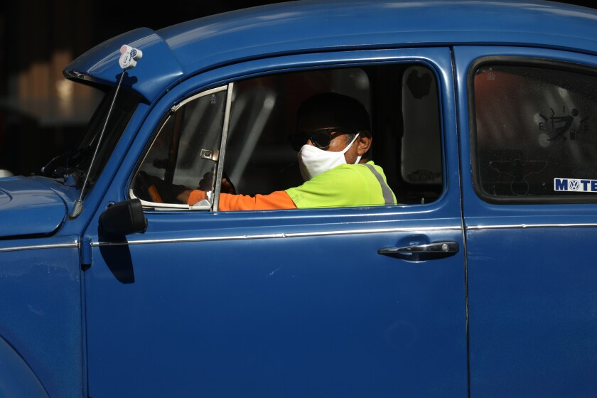 A masked driver in a VW in Old Towne Orange.  In Orange County, where many have refused to wear masks, COVID cases are up.