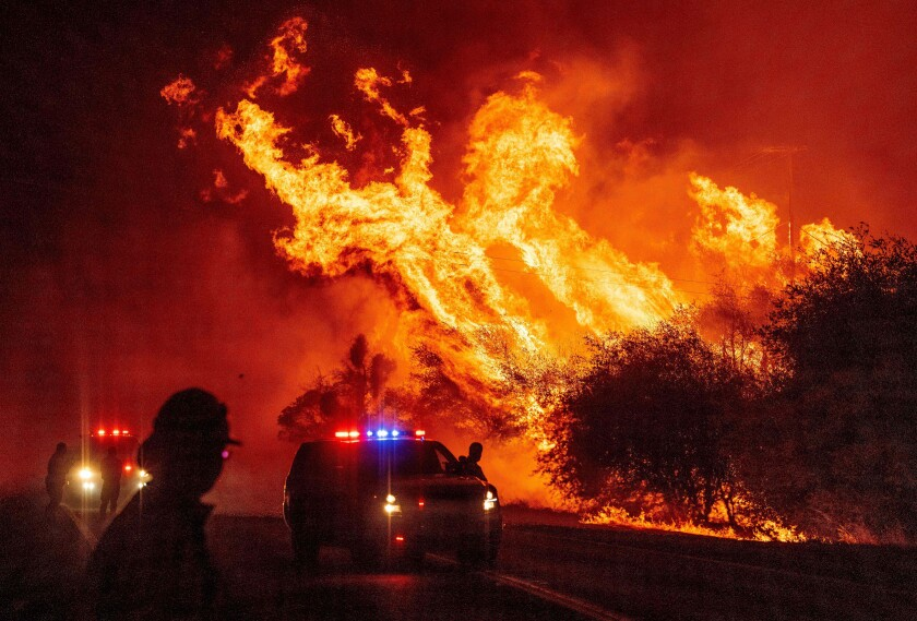 A law enforcement officer watches flames launch into the air from the Bear fire in Oroville, Calif.