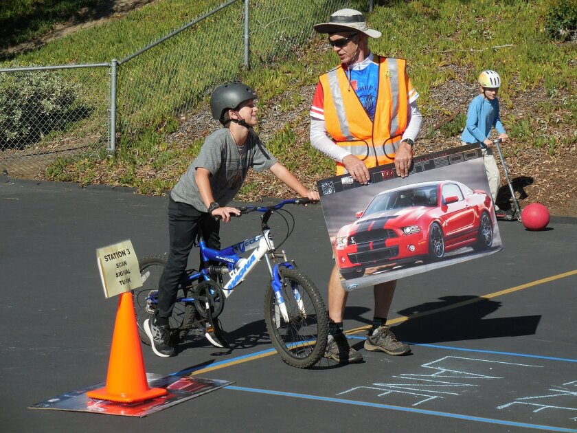 Karl Rudnick shows a child how to safely scan the road, signal and turn when riding his bicycle.