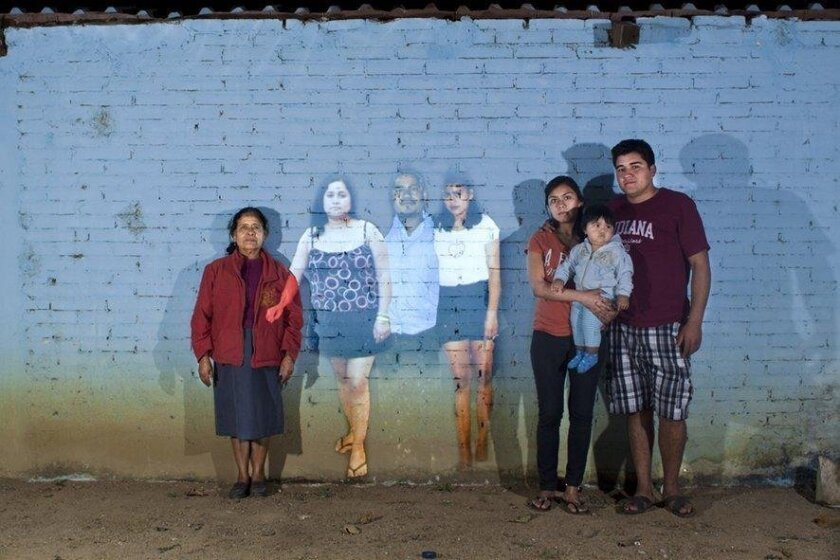 A projected image of family members who immigrated to the U.S. forms part of a new art exhibit at San Diego Mesa College, which examines the effects of migration to the U.S.