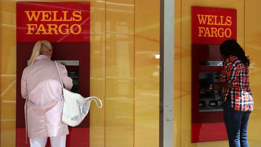 Customers use ATMs at a Wells Fargo Bank branch in San Francisco in July,