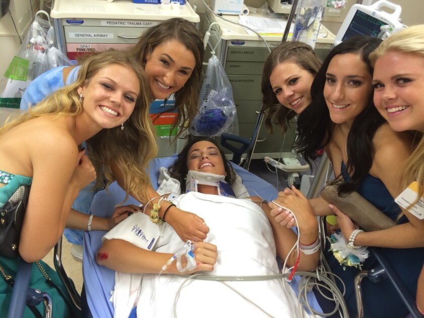 Charlotte Boyse, center, is surrounded by friends at the hospital after she fell out the window of a bus taking dozens of Corona del Mar High School students to prom.