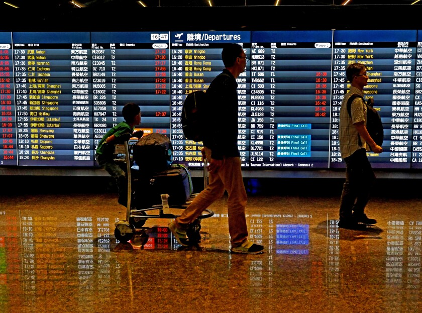 Passengers walk past a flight information board at the Taoyuan International Airport in Taoyuan County, northern Taiwan, on May 24, 2018.