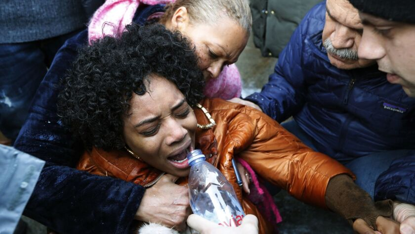 A woman is helped after she was pepper sprayed during a protest Sunday at the Metropolitan Detention Center in Brooklyn, N.Y.