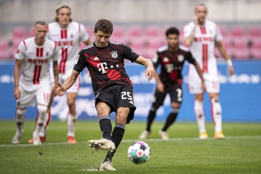 Thomas Mueller, izquierda, del Bayern Múnich, anota de penal el primer gol del equipo en un partido de la Bundesliga alemana contra Colonia el sábado, 31 de octubre del 2020. Bayern ganó 2-1. (Marius Becker/dpa vía AP)