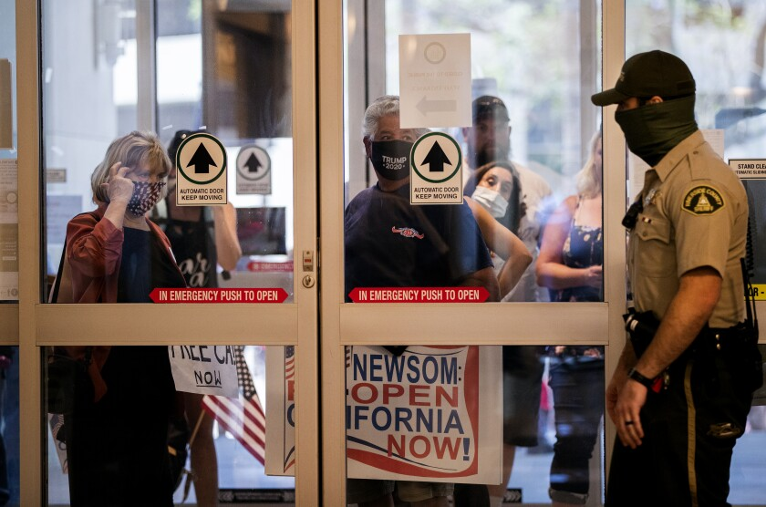 Residents who want public health orders rescinded wait to enter the County Administrative Center to speak during an emergency Riverside County Board of Supervisors meeting last week.