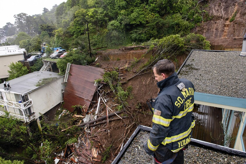 Patrick Young with the Southern Marin Fire Department looks out over the aftermath of a mudslide that destroyed three homes on a hillside in Sausalito.