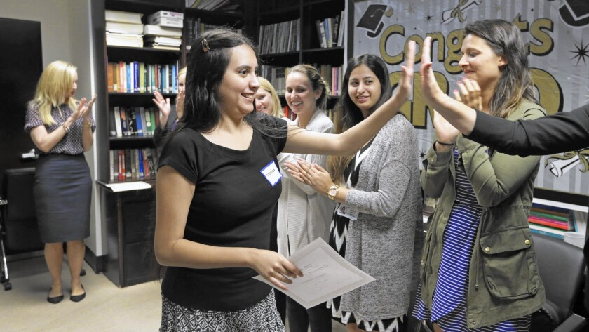 Monica Romero high-fives volunteers during her graduation ceremony from a 16-week course held at UCLA that helps young adults with autism build social skills.