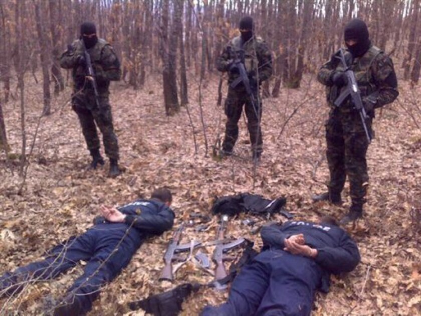 In a handout photo from the Serbian police, showing members of the Serbian gendarmerie, top, as they detain two armed policemen from Kosovo who allegedly crossed into Serbia in a border area, near Merdare, Serbia, Saturday, March 31, 2012. Police said in a statement that the two Kosovo policemen we