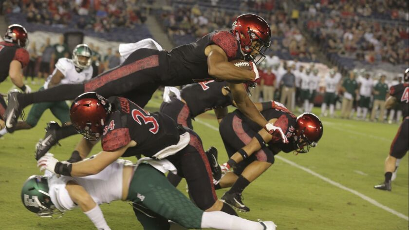 The Aztecs' Fred Trevillion is upended on the first kickoff return of the game. photo by Bill Wechter