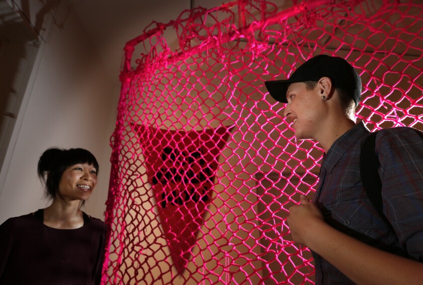 """Astria Suparak, curator of the exhibition Alien She, chats with artist LJ Roberts standing next to the crank-knit yarn, hand-woven wire, steel poles hardware piece titled """"We Couldn't Get In. We Couldn't Get Out"""" at the Orange County Museum of Art in Newport Beach."""