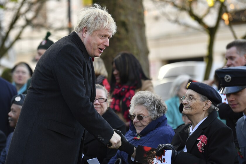 Britain's Prime Minister Boris Johnson, left, greets a veteran, as he attends a remembrance service on Armistice Day, the 101st anniversary of the end of the First World War, in Wolverhampton, England, Monday, Nov. 11, 2019, while on the General Election campaign trail. (Ben Stansall/Pool Photo via AP)