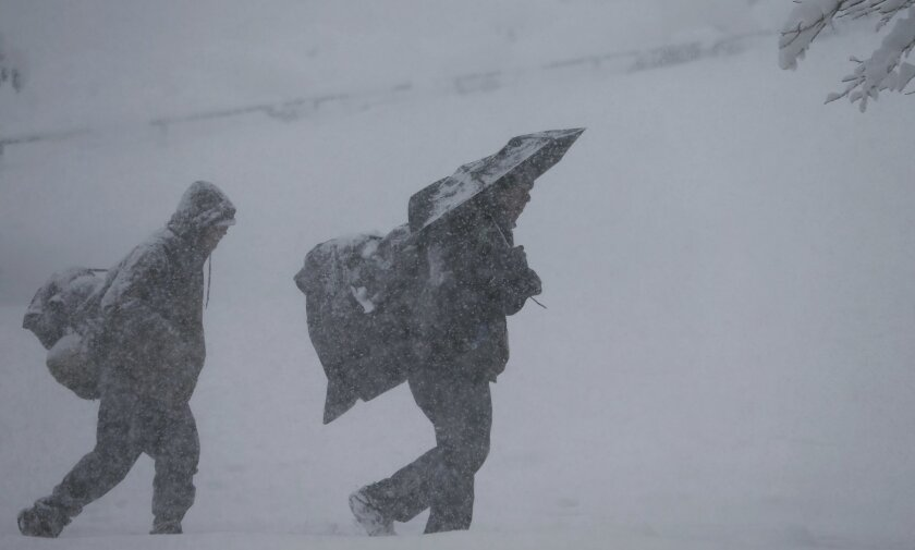 Pedestrians struggle to climb the hill south of the State Capitol as a spring storm packing high winds and wet, heavy snow blanketed Denver Wednesday, March 23, 2016. The wet, heavy snow and strong winds have crippled travel in north central Colorado, shutting down some highways and schools and even Denver's airport. (AP Photo/David Zalubowski)