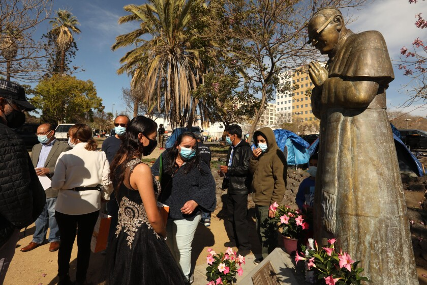 People gather around and near a statue of Archbishop Oscar Romero.