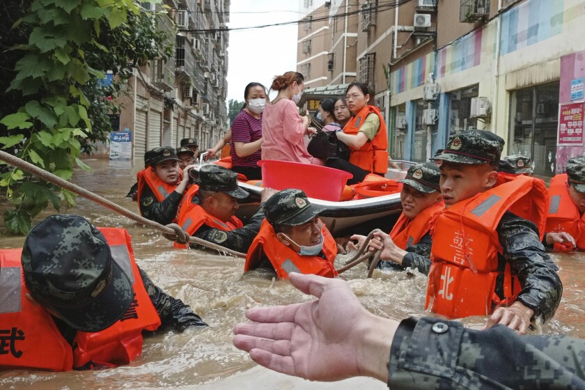 FILE - In this Thursday, Aug. 12, 2021 file photo, paramilitary police work to evacuate people trapped in a flooded area in Suizhou in central China's Hubei Province. Flooding in central China continued to cause havoc in both cities and rural areas. A United Nations report released on Tuesday, Oct. 5, 2021 forecasts that more than 100 countries lack the infrastructure to deal with worsening floods and drought expected to come with climate change. (Chinatopix via AP)