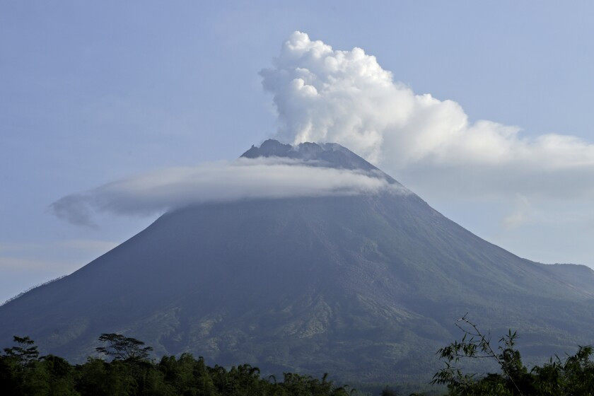 Mount Merapi spews volcanic steam from its crater seen from Sleman, Yogyakarta, Indonesia, Thursday, Jan. 7, 2021. The 2,968-meter (9,737-foot) mountain spewed avalanches of hot clouds on Thursday morning amid its increasing volcanic activities. (AP Photo/Taufiq Rozzaq)