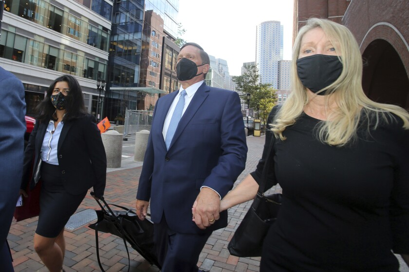 FILE — In this Monday, Sept. 13, 2021 file photo, John Wilson, center, holds his wife's hand, right, as he departs federal court, in Boston. Wilson and another parent, Gamal Abdelaziz, who are the first to stand trial in the college admissions bribery scandal, used lies and money to steal coveted spots at prestigious schools their kids couldn't secure on their own, a prosecutor said Wednesday, Oct. 6, 2021, before jurors decide if the men are guilty. (AP Photo/Stew Milne, File)