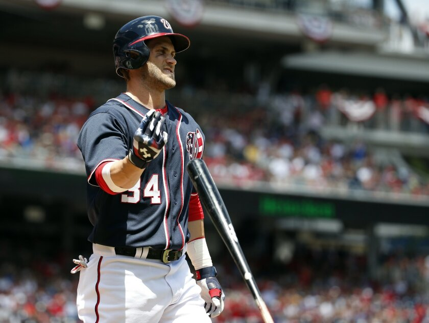 Washington Nationals' Bryce Harper (34) tosses his bat after striking out during the fifth inning of a baseball game against the Chicago Cubs at Nationals Park, Friday, July 4, 2014, in Washington. (AP Photo/Alex Brandon)
