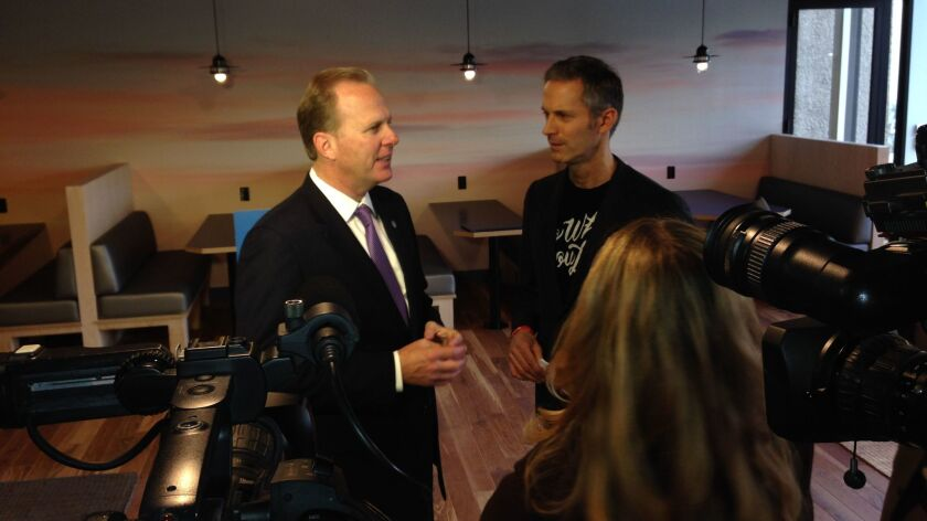 Mayor Kevin Faulconer, left, and Jon Slavet, western regional manager for WeWork, chat at Thursday's official opening of the company's downtown headquarters.