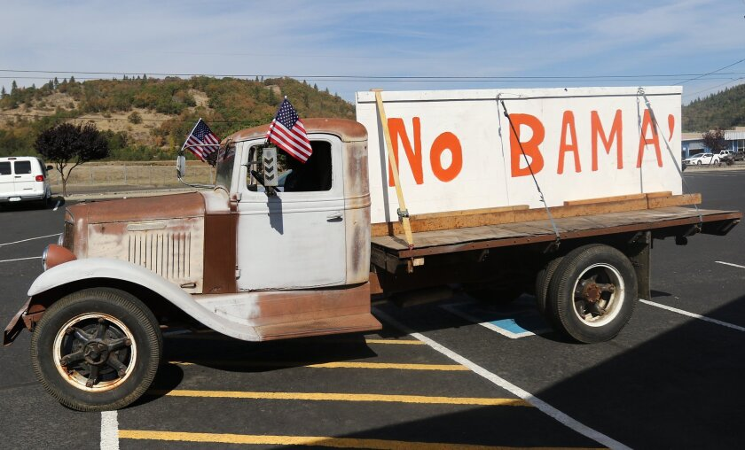 Gary Shamblin of Winston, Ore., prepares to leave a parking lot in Roseburg in his truck displaying a sign he made reflecting his views on President Obama's planned visit to the area.