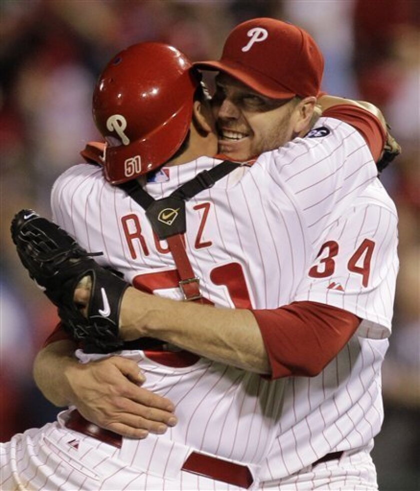 Philadelphia Phillies starting pitcher Roy Halladay celebrates with catcher Carlos Ruiz (51) after throwing a no-hitter to defeat the Cincinnati Reds 4-0 during Game 1 of baseball's National League Division Series Wednesday, Oct. 6, 2010, in Philadelphia. (AP Photo/Rob Carr)