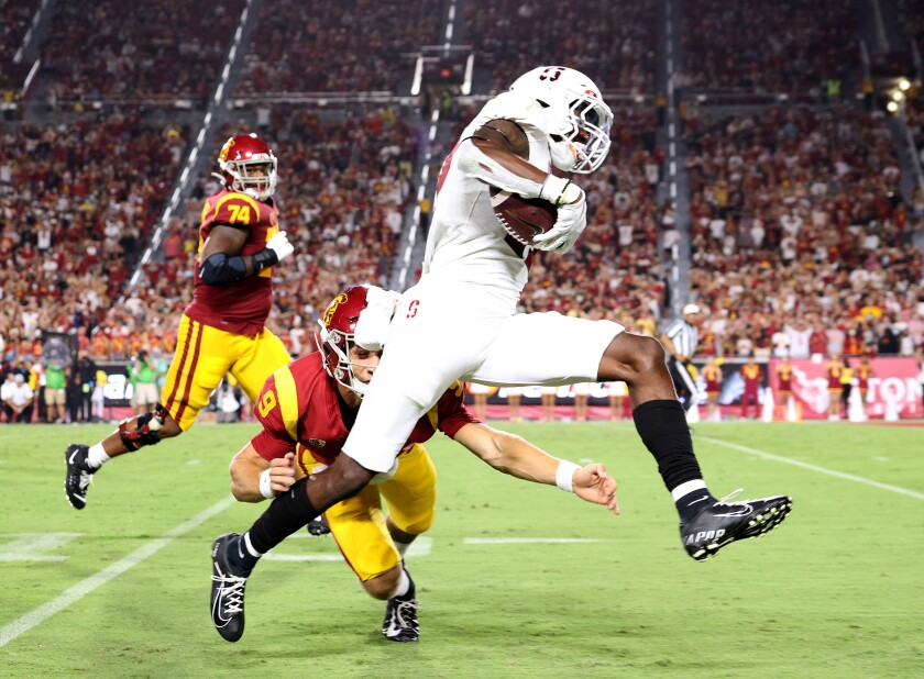 Stanford's Kyu Blu Kelly sprints past USC quarterback Kedon Slovis on a interception return for a touchdown.