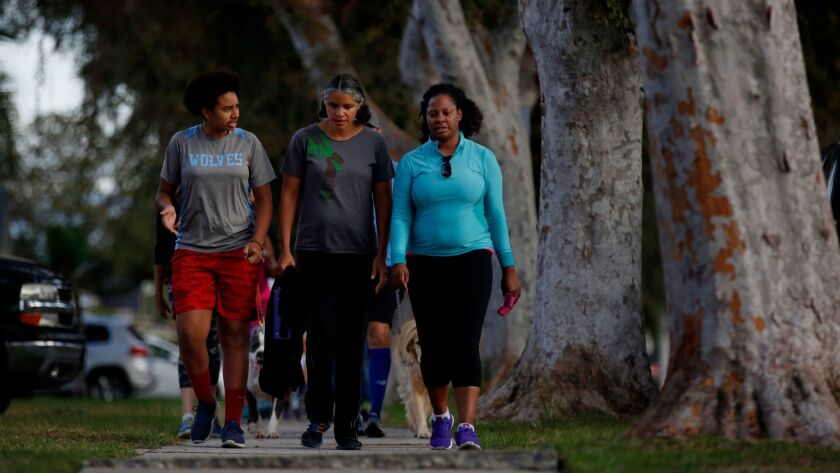 From left, Moreau Halliburton, Monique Marshall and Mikaela Randolph walk together in Leimert Park.