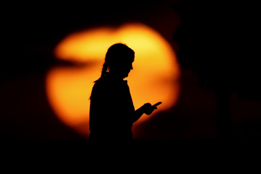 FILE - In this Monday, June 29, 2020, file photo, a woman looks at her phone in a park as the sun sets in Kansas City, Mo. On Wednesday, Sept. 15, 2021, a divided federal appeals court upheld the dismissal of an ACLU lawsuit challenging a portion of the National Security Agency's warrantless surveillance of Americans' international email and phone communications. (AP Photo/Charlie Riedel, File)