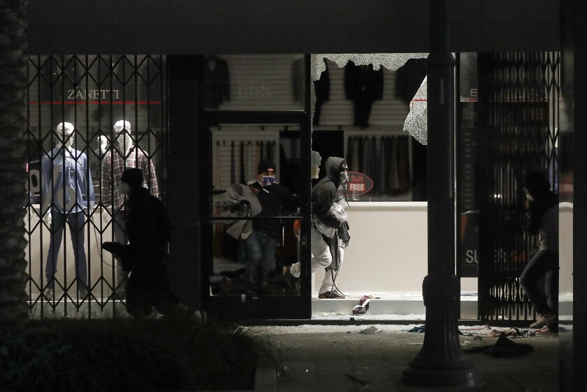 Looters ransack a clothing store on Pine Avenue in Long Beach on Sunday.